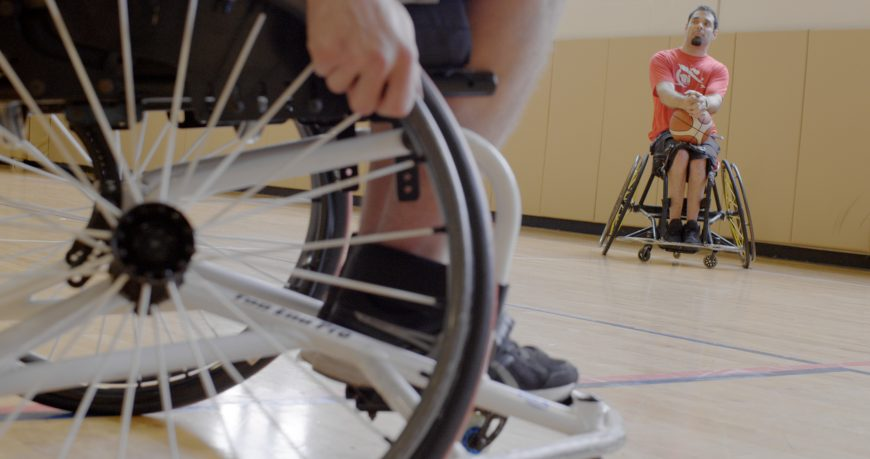 Close of of wheelchair wheels in front, and Coach Paul in the background holding basketball