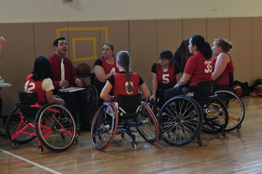 Picture shows Coach Paul with group of women's wheelchair basketball players in red jerseys having a team meeting