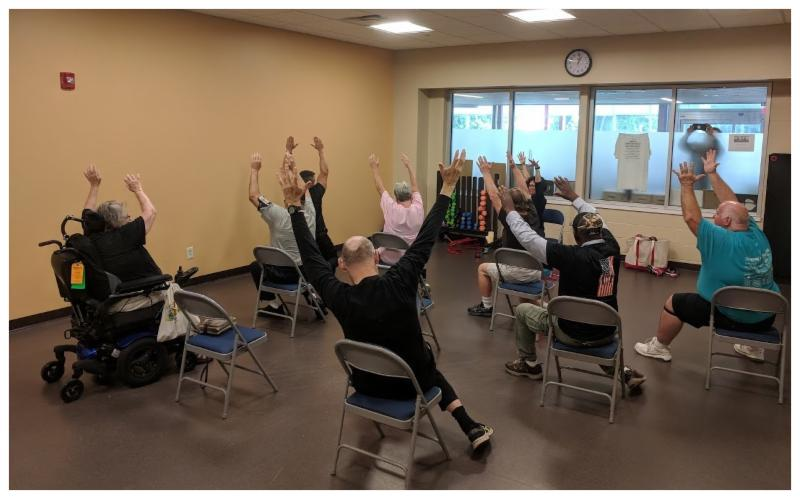 Picture of adaptive yoga class, participants stretching in chairs or standing and stretching